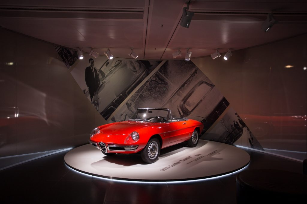 A red Alfa Romeo Spider from 1966 sites on a turntable in a museum.