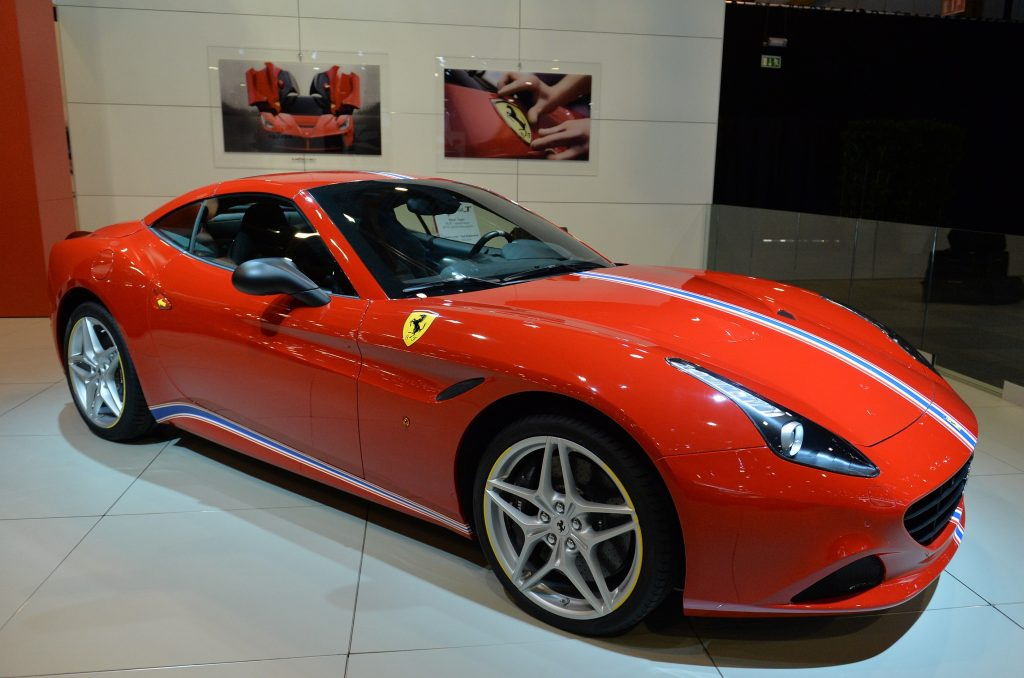 A red Ferrari California T sits on display at a car show