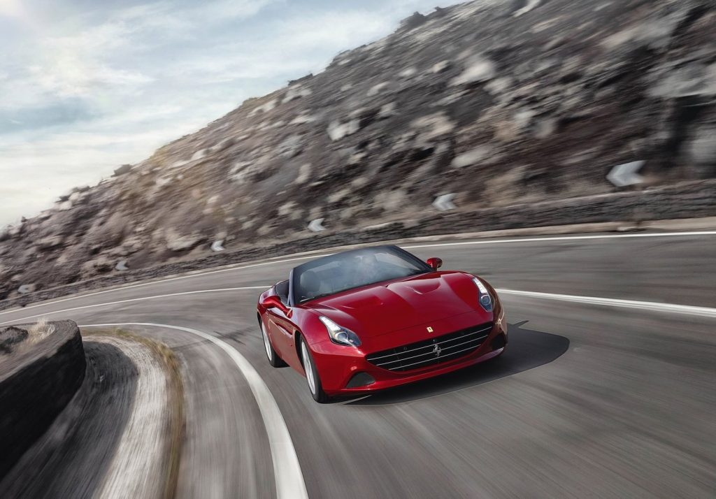 a red Ferrari driving fast on a winding mountain road