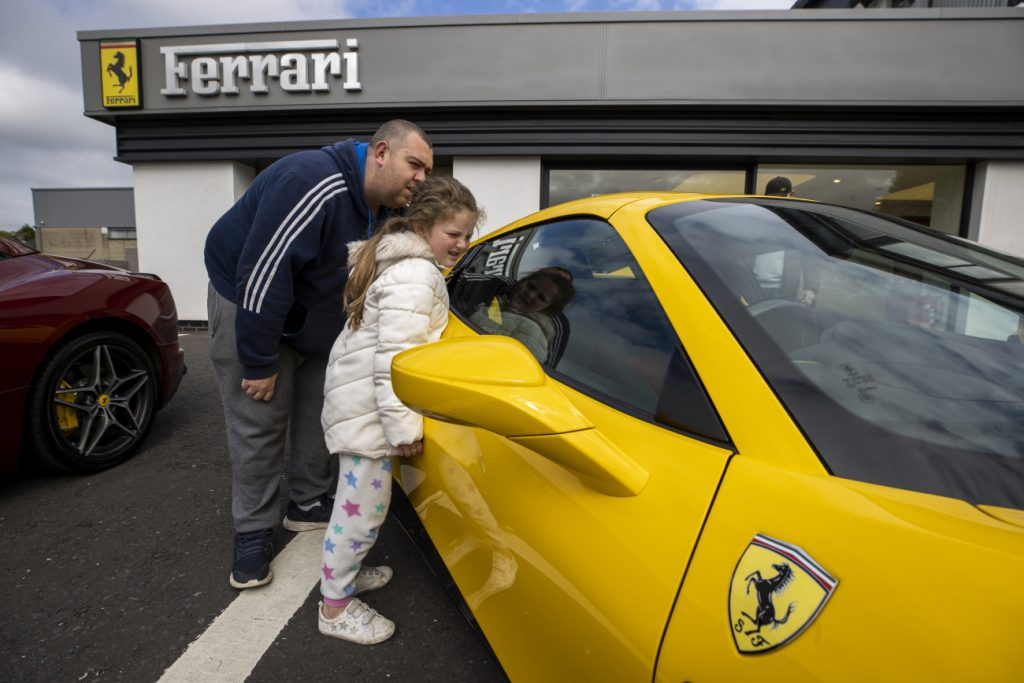 A father and his daughter looking at a new yellow Ferrari