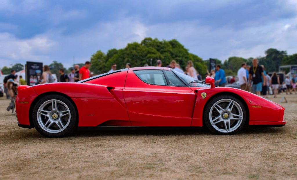 A rare Ferrari Enzo in red on a lawn at a a car show