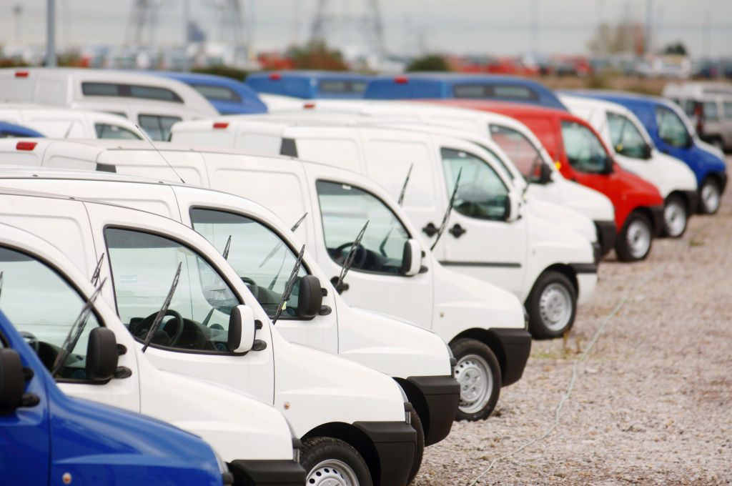 White Fiat cargo vans lined up for delivery in the UK in the