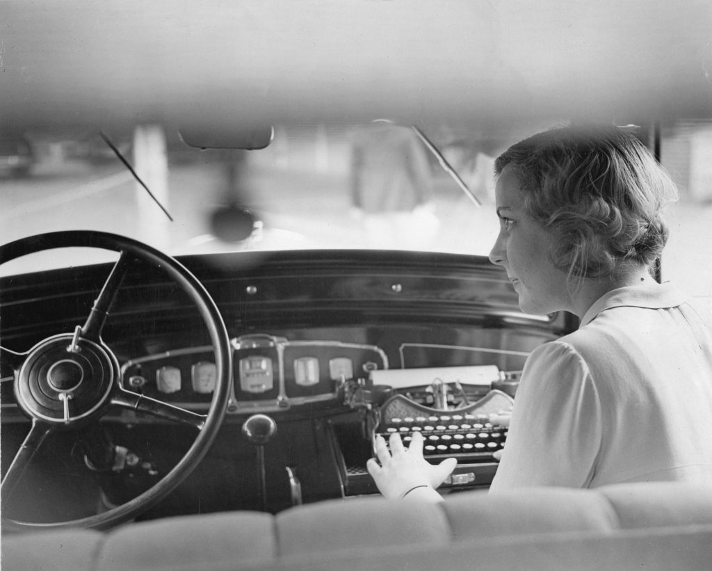 A lady sits in a car at an early automotive workstation for writers.