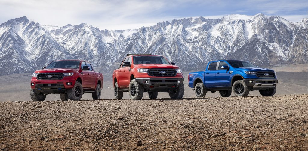 Red Level 2, orange Level 3, and blue Level 1 Ford Performance-modified Rangers in front of a mountain range