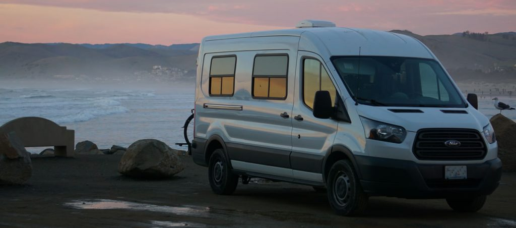 A Ford Transit van that has been converted for vanlife sits by the beach.