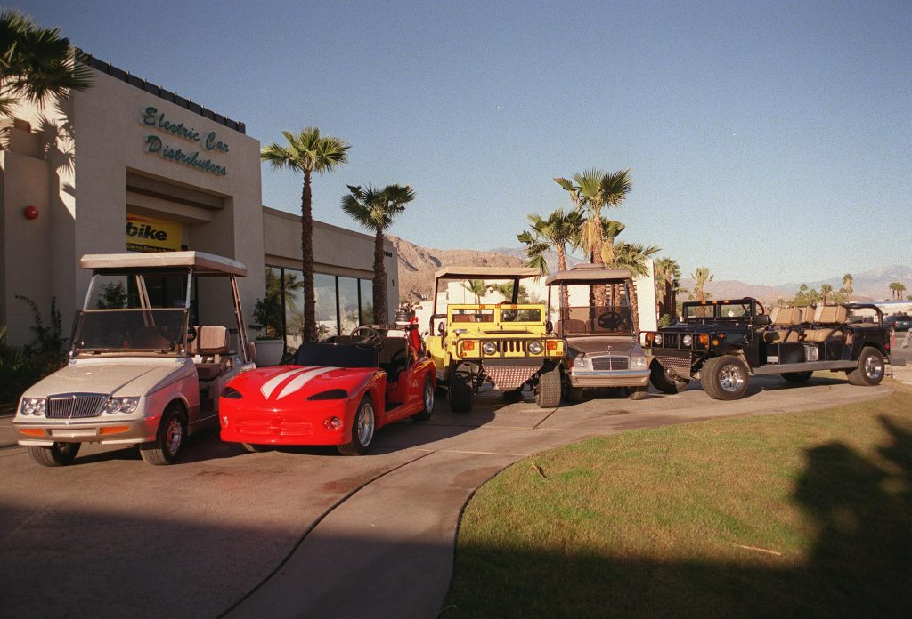 A selection of custom golf carts are on display at a dealership