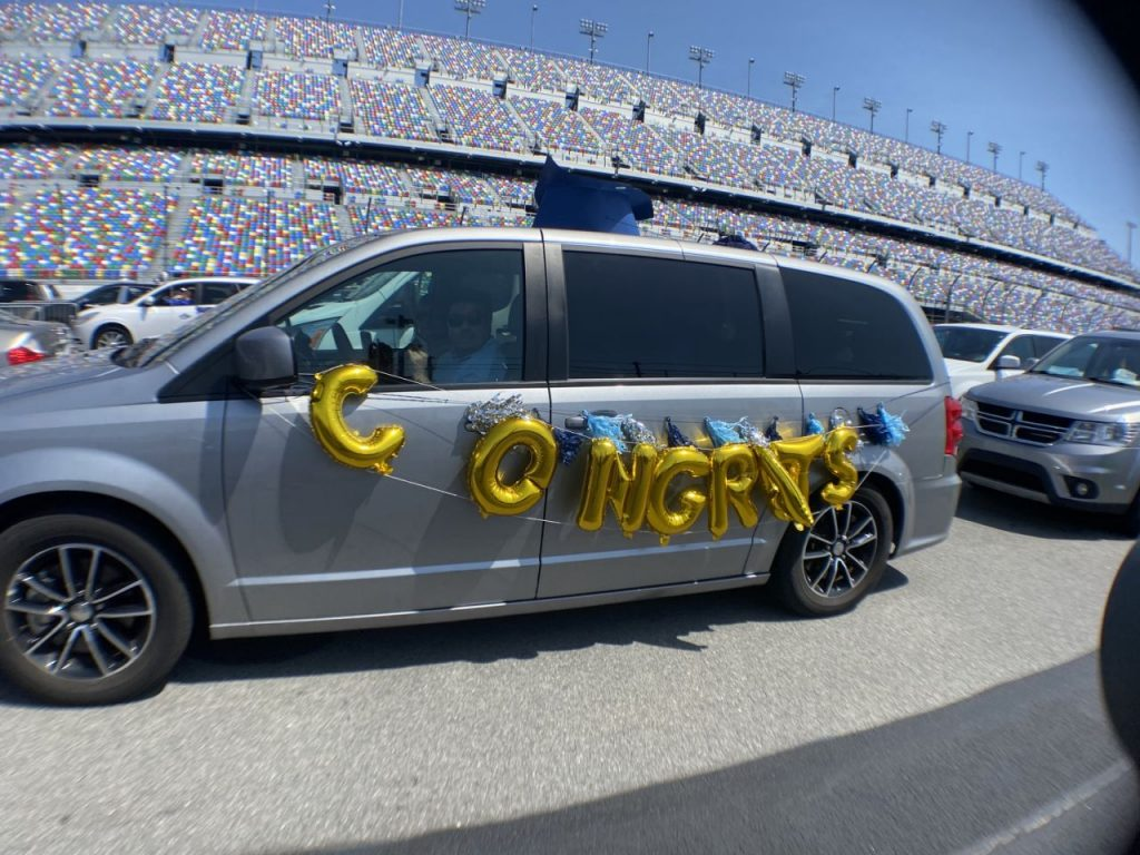 A minivan is decorated to honor a high school senior that is graduating at a ceremony at Daytona International Speedway