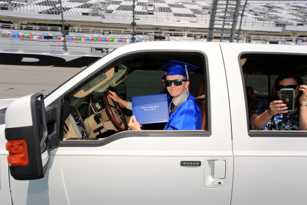 A high school senior in cap and gown shows the diploma he received at Daytona International Speedway