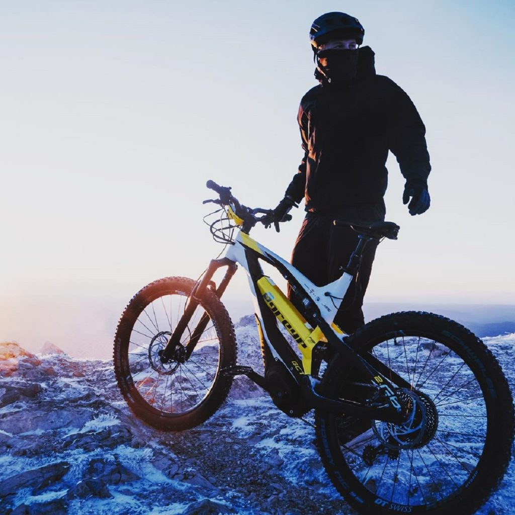 White-and-yellow Greyp G6 electric mountain bike on top of a snowy mountain facing the sunrise