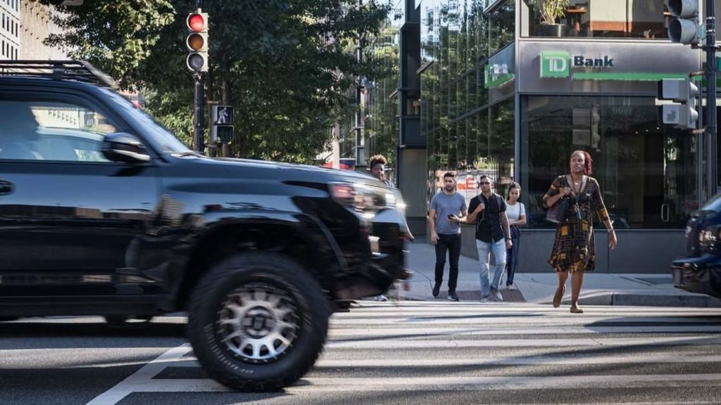An SUV drives close over a pedestrian crossing in a city