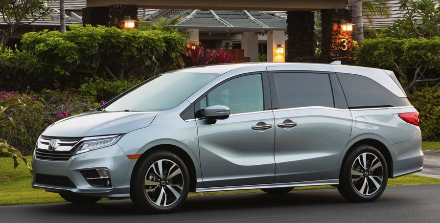 a silver Honda Odyssey parked in front of an upscale residence