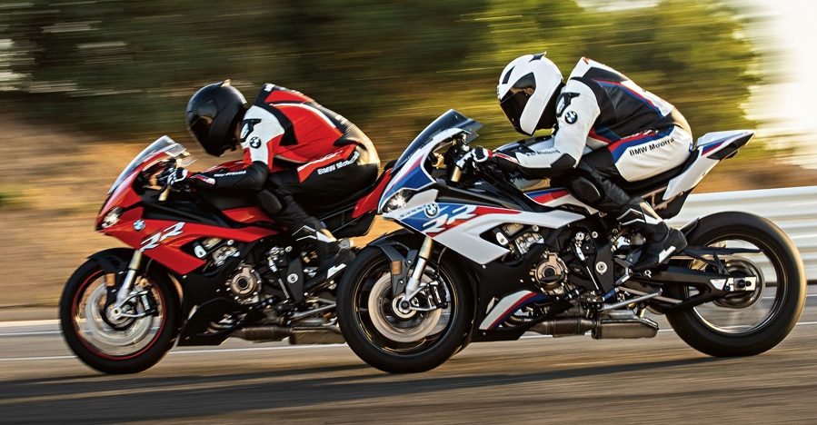 2 2020 BMW S1000RRs, one red and one red-white-and-blue, race side-by-side