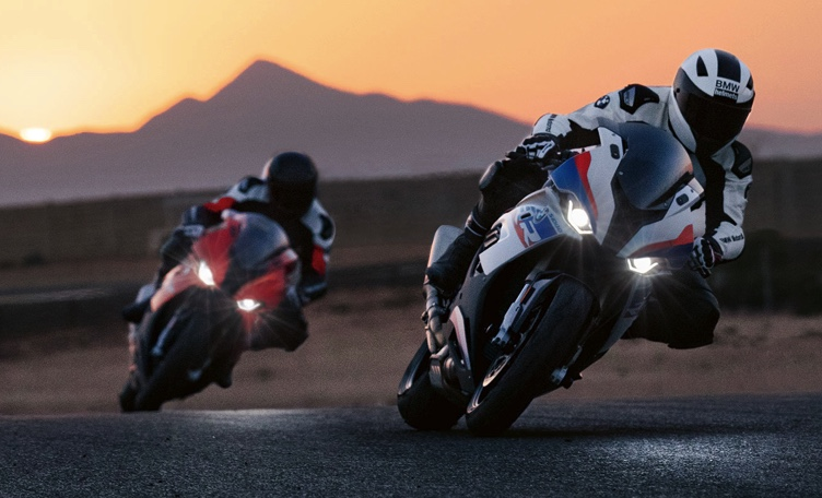 two 1-liter BMW sportbikes opening up the throttle on a desert racetrack.