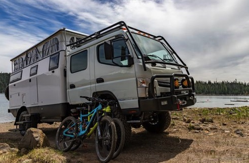 EarthCruiser dual cab RV with the family bikes leaning up against the cab