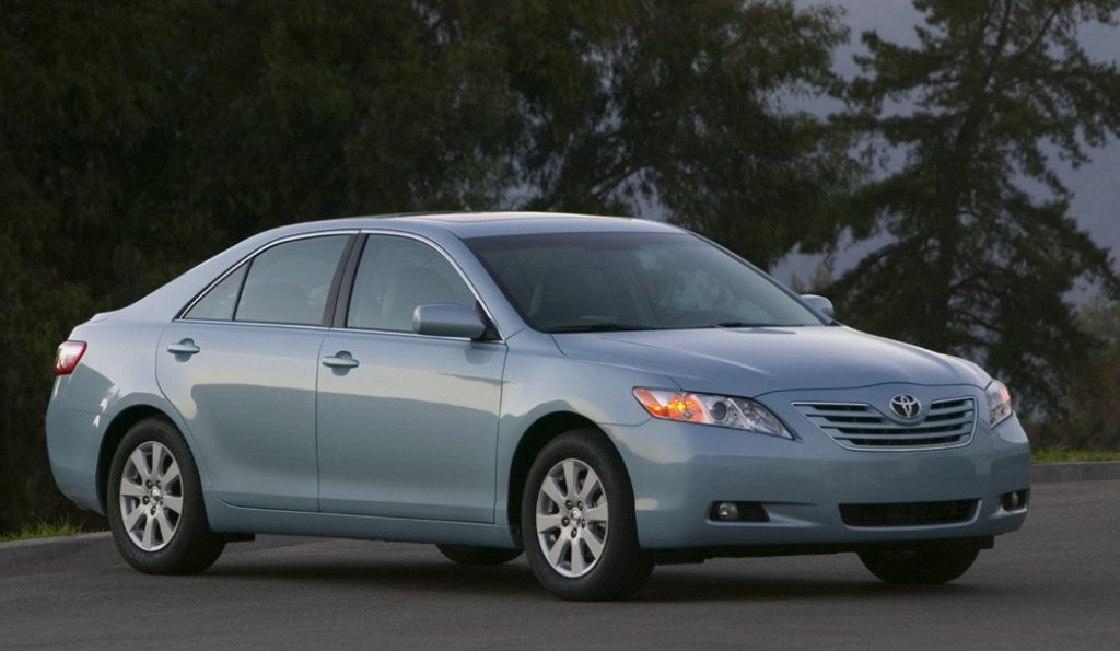 a 2007 Toyota Camry was a great car new, and its still great used. This light blue one is parked on the street in front of some gorgeous trees.