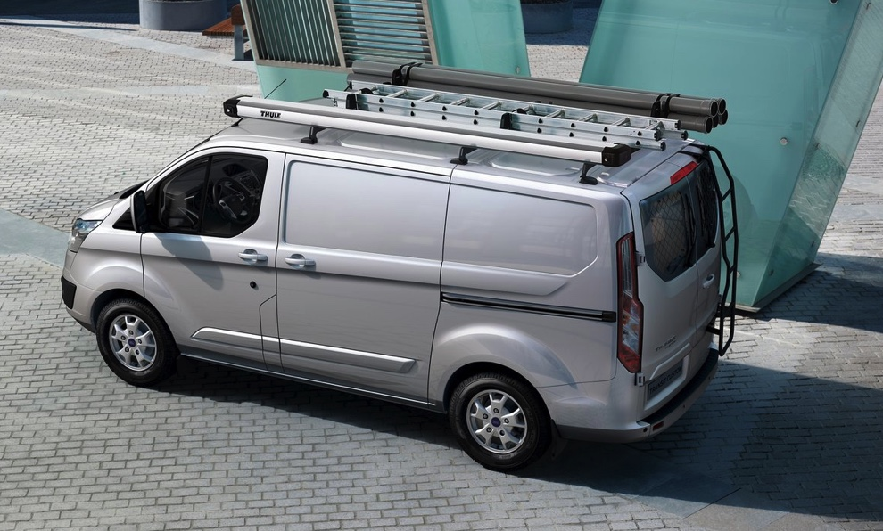 A gray Ford Transit with a custom roof mount driving through the city