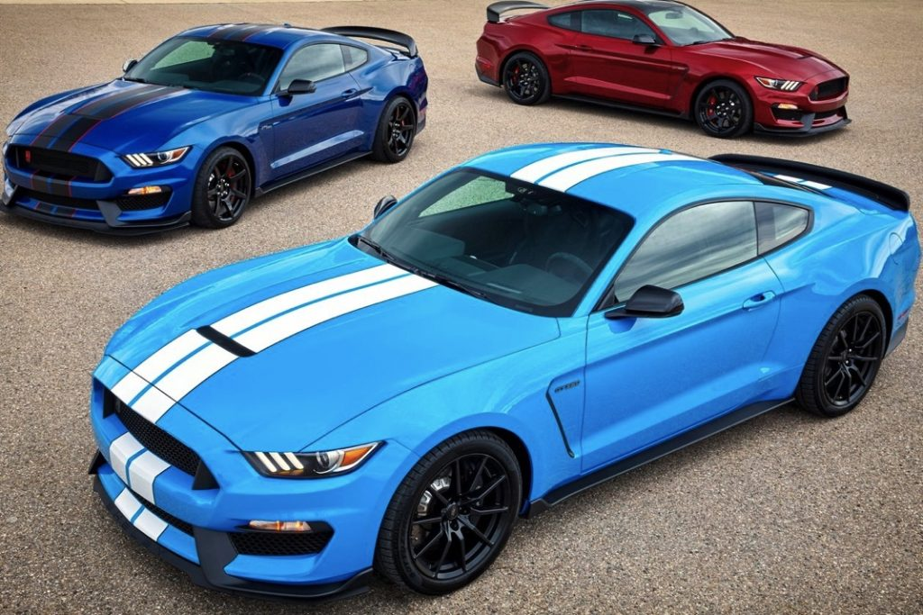 three Mustang GT350s. A red one and dark blue with a candy blue 2017 Ford Mustang in the foreground