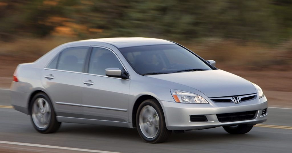 a silver seventh gen Honda Accord driving on a scenic road