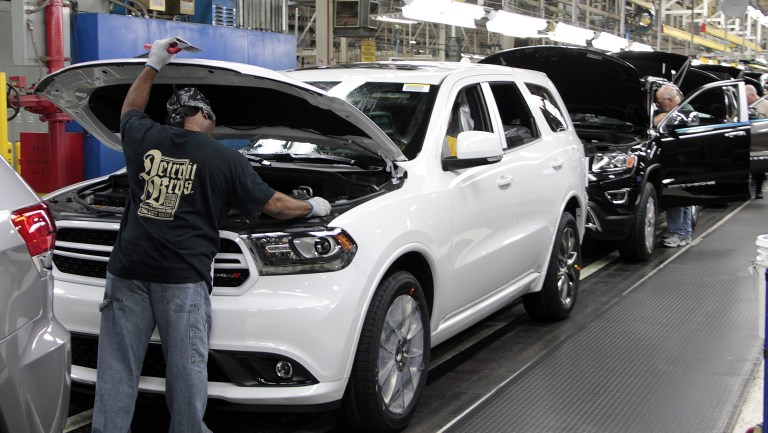 man under the hood of a white Durango on the assembly line