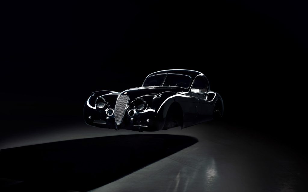 The shell of classic, black, Jaguar XK 120 that is being converted to electric power