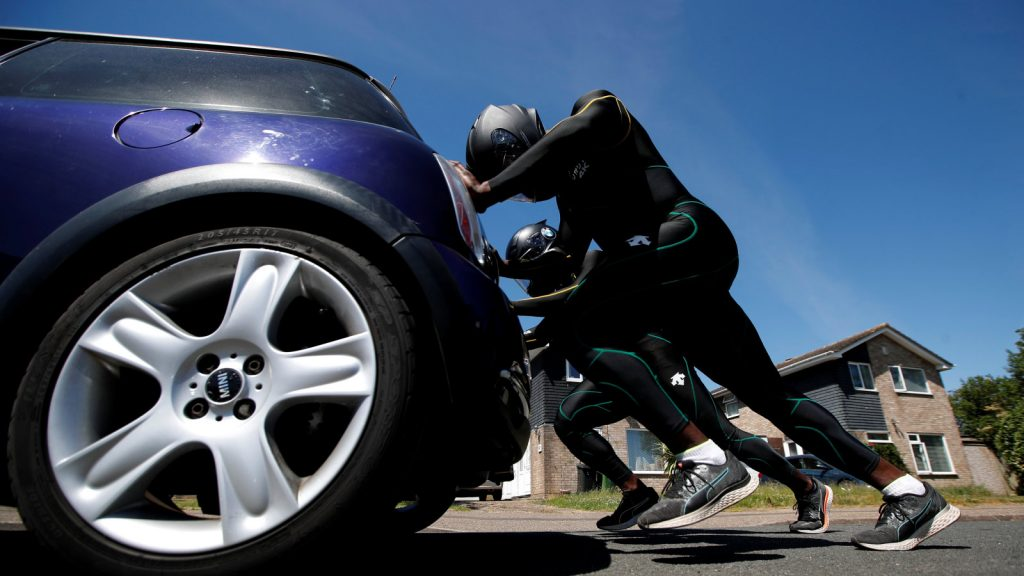 Two team members in team uniform push a blue Mini Cooper