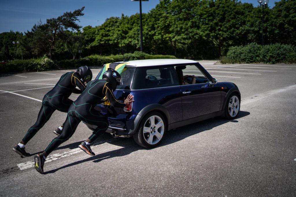 Two team members in team uniform push a blue Mini Cooper through a parking lot.