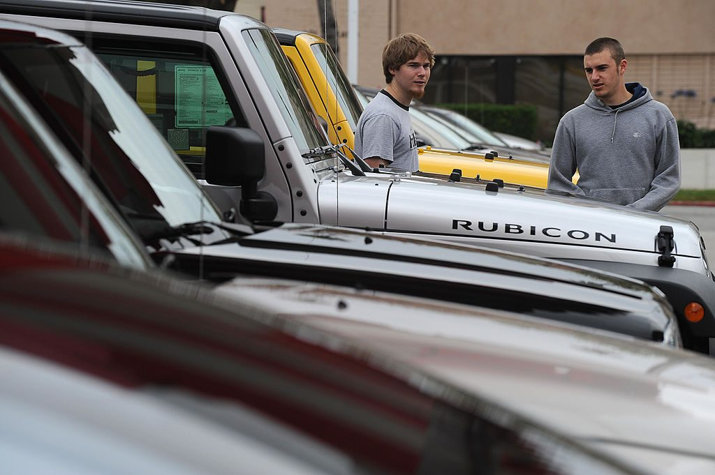Car shoppers inspect a row of Jeep Wranglers