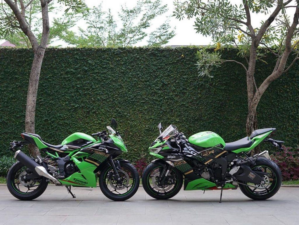 Green Kawasaki Ninja 250 SL next to green Ninja ZX-25R, in front of a hedge