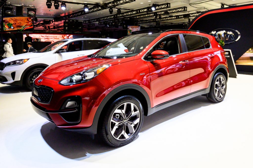 A red Kia Sportage on display at an auto show