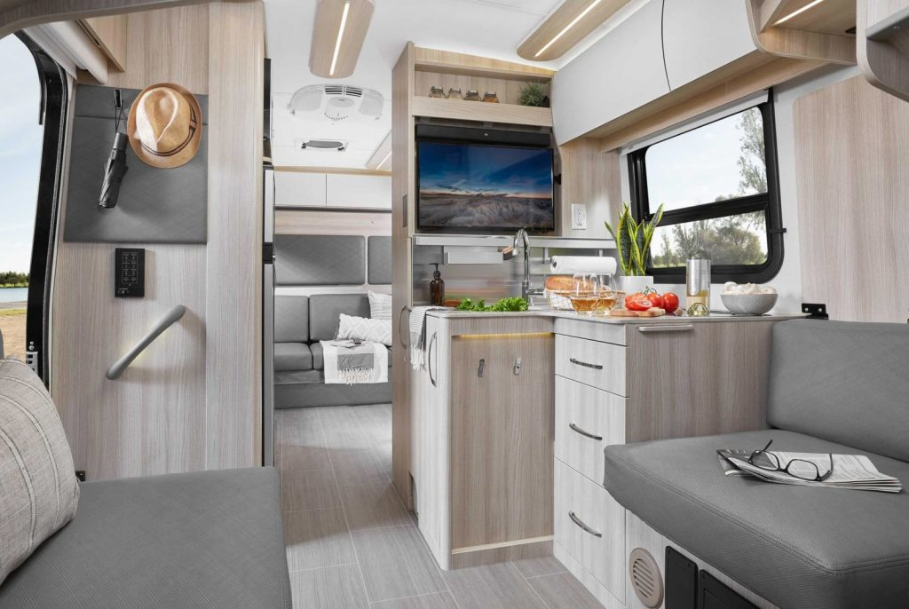 A view of the kitchen, the counters, and seating within the RV