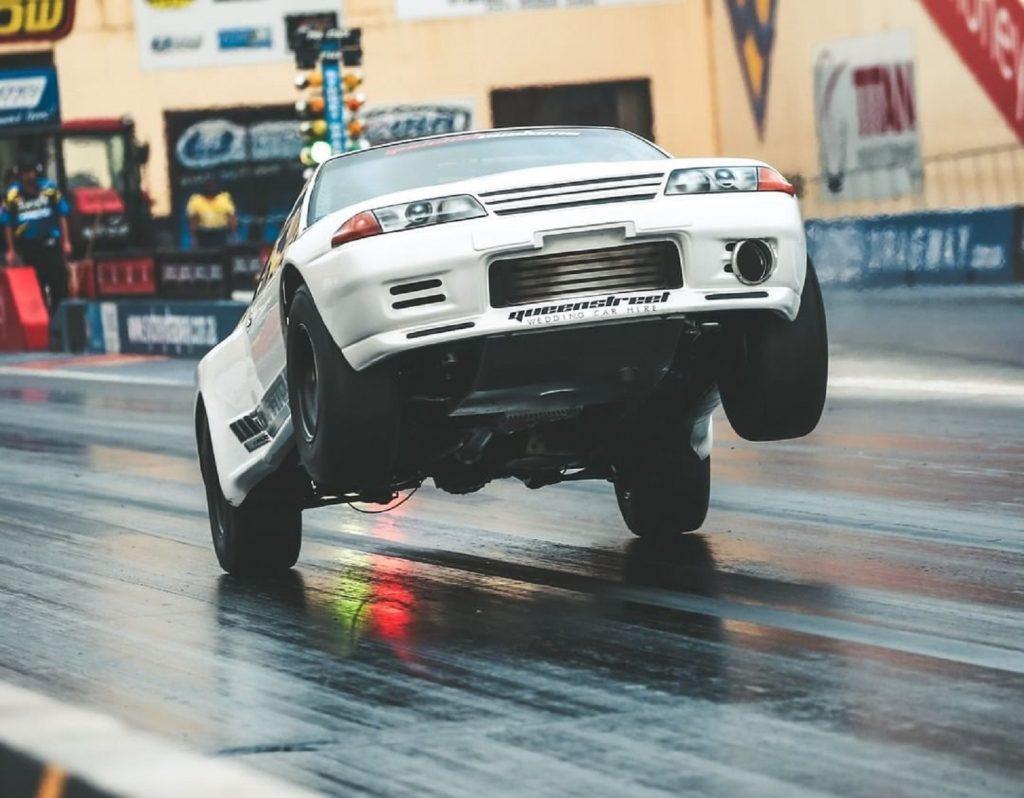 Maatouks Racing's white 2100-hp R32 Nissan Skyline GT-R drag race car pulling a wheelie on the drag strip