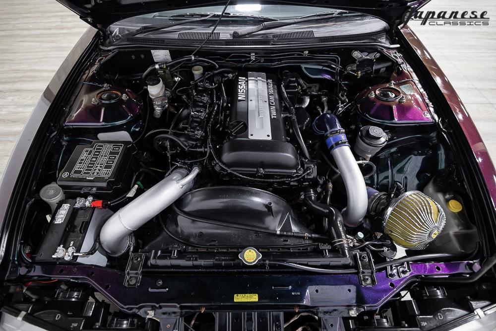 The engine bay of a modified purple 1995 S14 Nissan Silvia