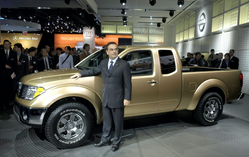 Nissan President and CEO Carlos Ghosn poses with the new 2005 Frontier pickup truck after a news conference at the North American International Auto Show