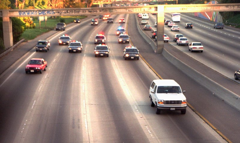 The white Ford Bronco in the OJ Simpson police chase driving down an LA highway in traffic.