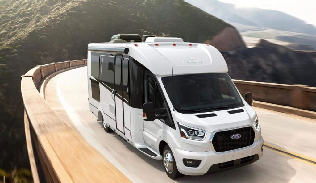 A large new RV motor home driving up a winding mountain pass