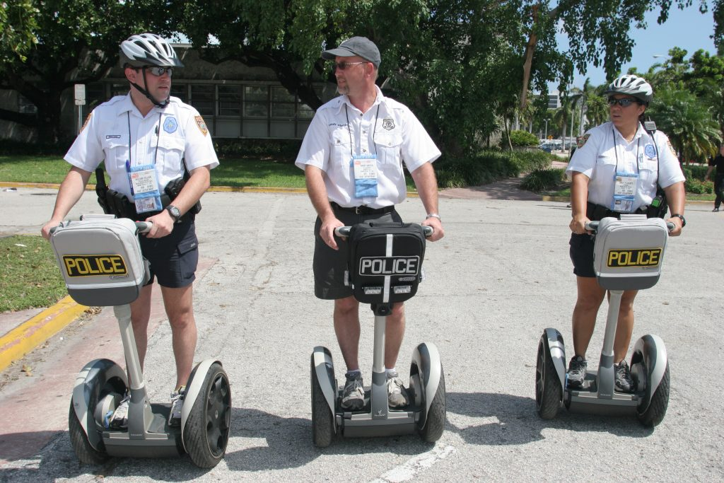 Three police officer ride Segways scooters as part of training.