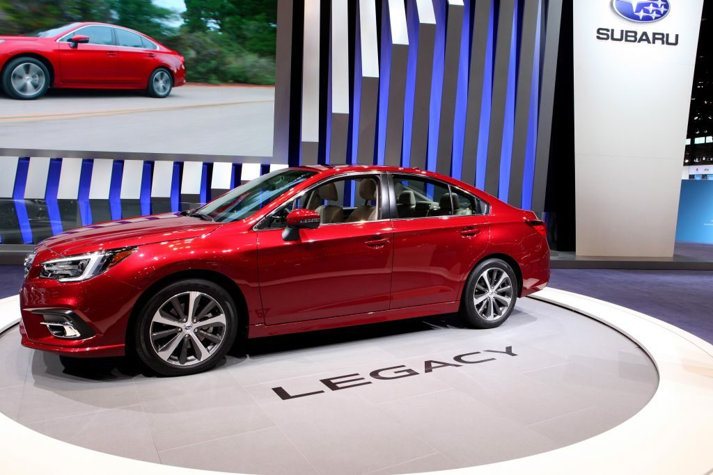 A red 2018 Subaru Legacy on display at an auto show