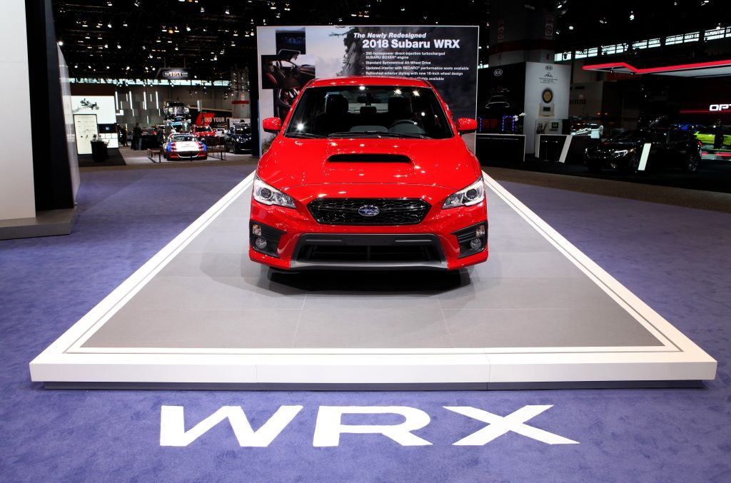 A red Subaru WRX on display at an auto show