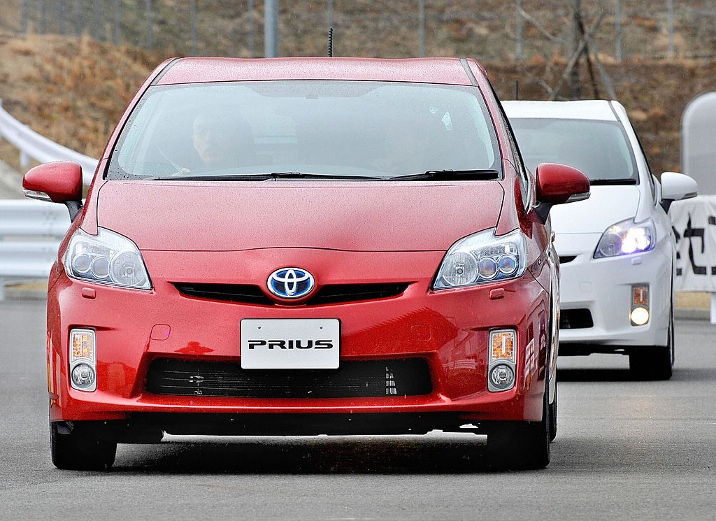 A Toyota Prius driving down the road