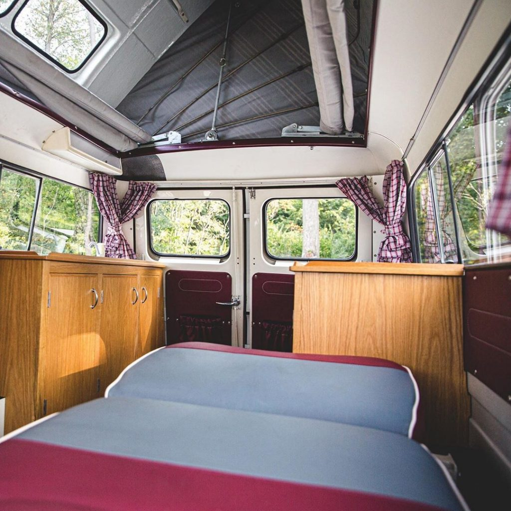 The restored interior of a 1961 Bedford CA Dormobile, showing the wood-paneled fridge, sink, and stove, and pop-up tent