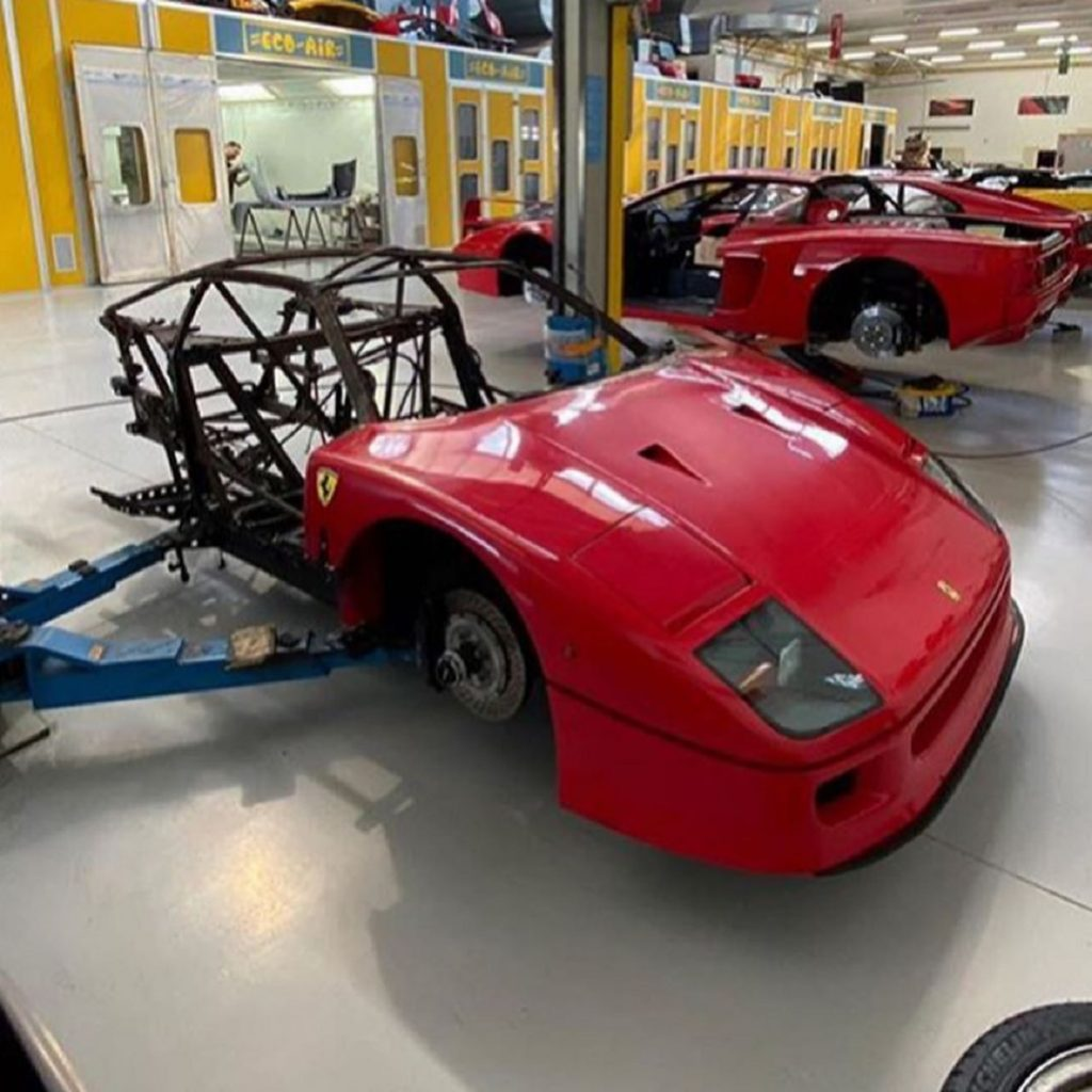 Red burned-out Ferrari F40 awaiting restoration in a shop