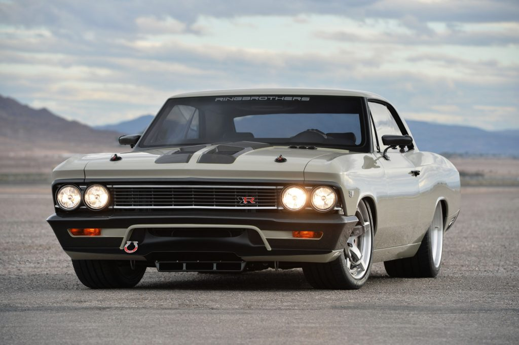 A custom gray Chevy Chevelle is parked with the headlights on