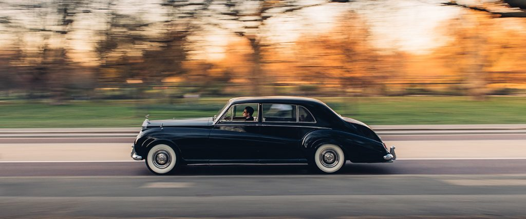 A black classic Rolls-Royce Phantom that has been converted to electric power is on the road at speed
