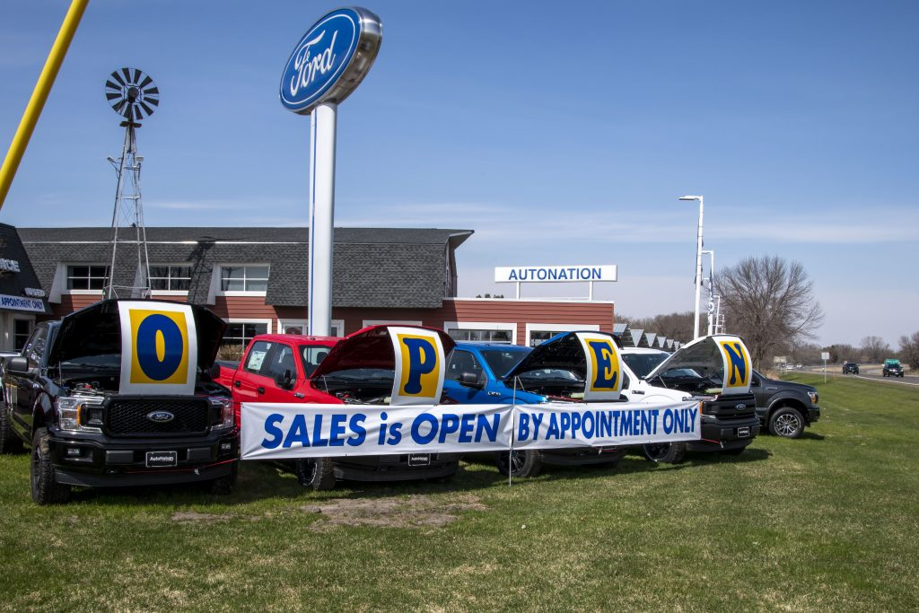 A banner in front of a dealership says, by appointment only.