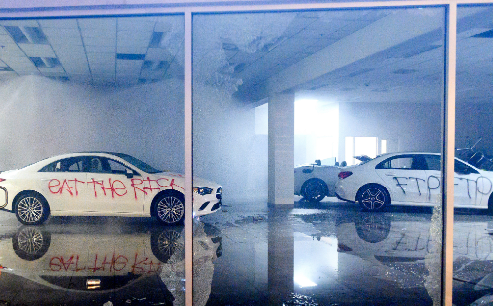 Aftermath of dodges vandalized inside of dealership with grafitti written in red spray paint
