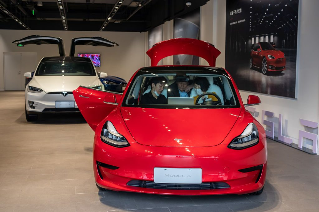 People sit in a Tesla Model 3 car at the first Tesla Center in Shanghai on May 9, 2020