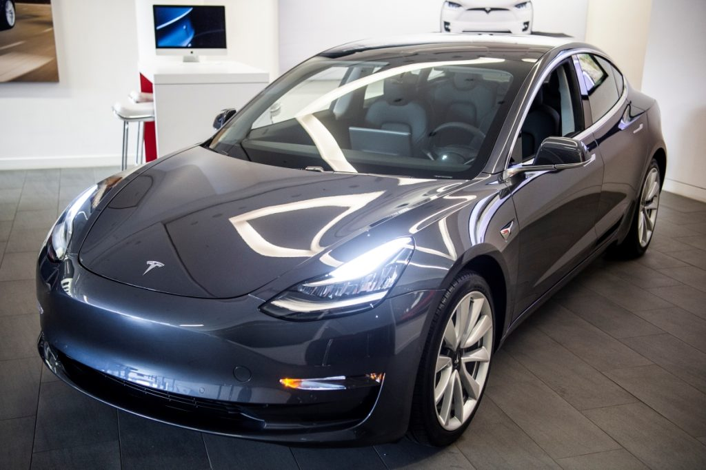 A charcoal Tesla Model 3 electric car in a showroom
