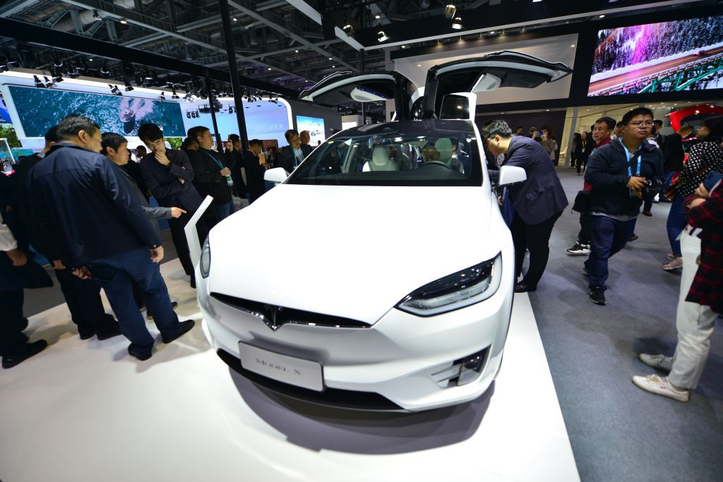 People watch Tesla Model X at Tesla booth on day three of the 2nd China International Import Expo (CIIE) at the National Exhibition and Convention Center