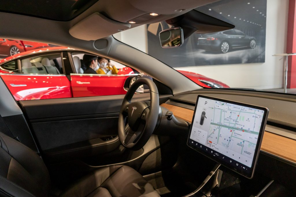 Citizens watch three models of Tesla Model 3, model X and model s in the exhibition hall of the newly opened Tesla experience center