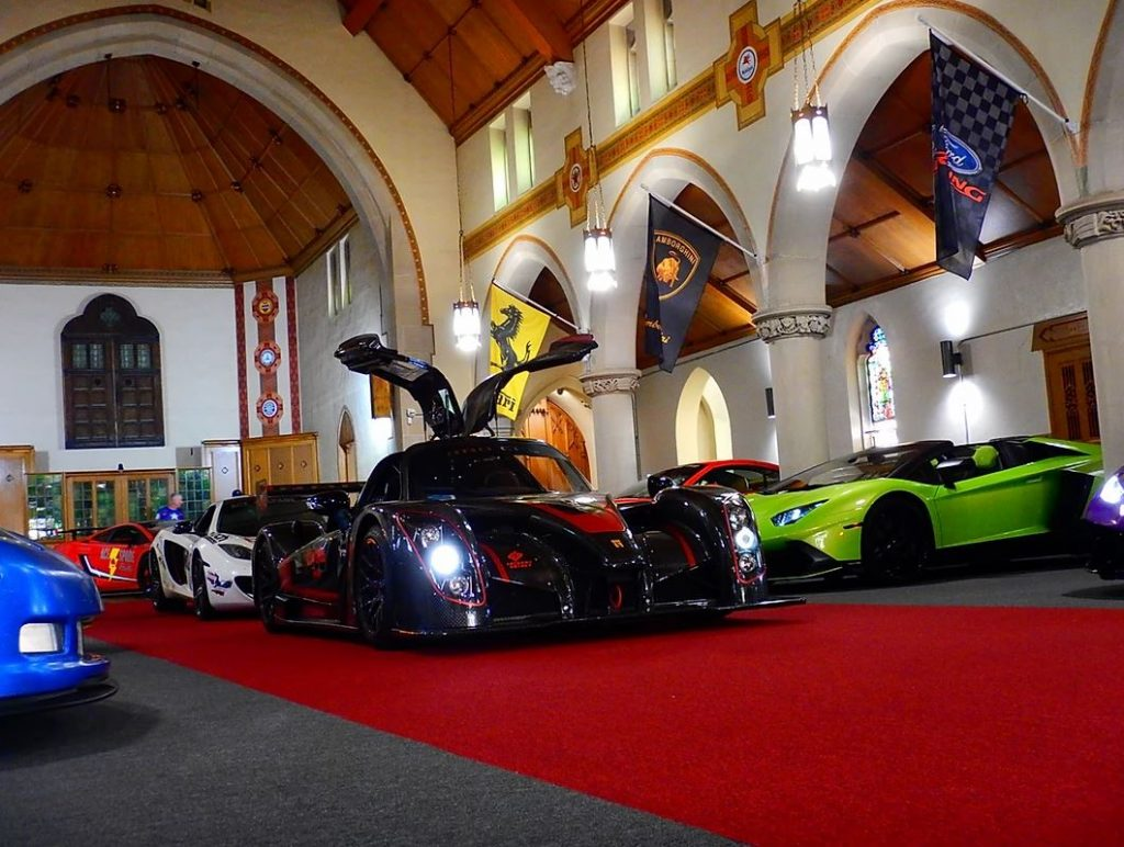 Cars line the inside of a converted church.